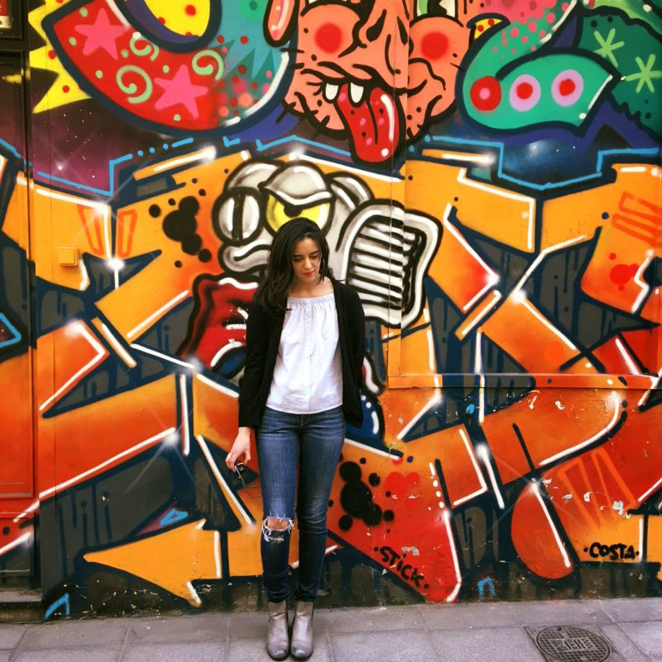 Photo d'Anissa Bouderbal devant un mûr tagué