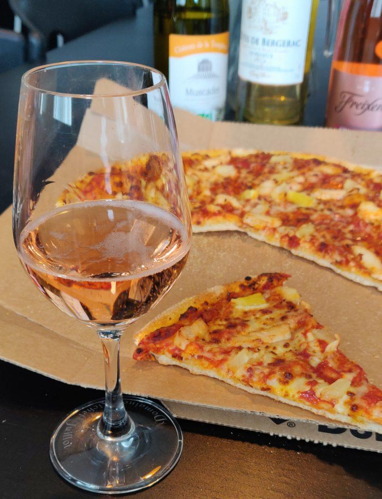Photo d'une pizza hawaïenne avec un verre de Cava rosé effervescent