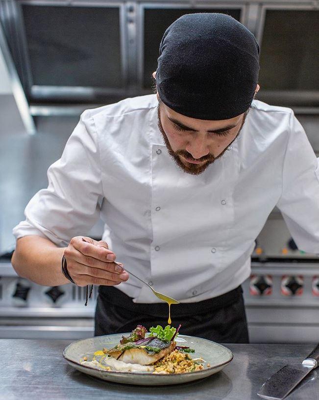 Le chef du restaurant les assembleurs, Mario dans la cuisine en train de saucer un plat.