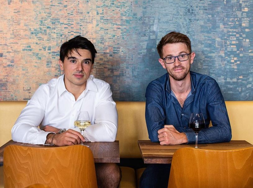Antoine et grégoire, les deux fondateurs de Les Assembleurs, assis dans la restaurant avec chacun un verre de vin.