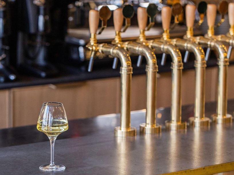 Les tireuses à vin du bar les assembleurs avec un verre de vin blanc.