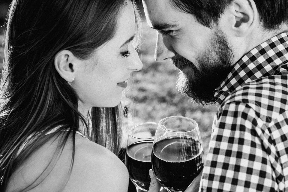 Couple heureux qui boit un verre de vin rouge