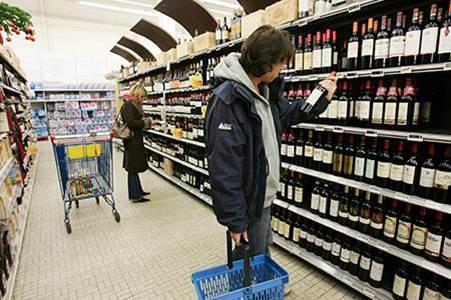 Homme qui essaie de choisir une bouteille de vin dans un supermarché