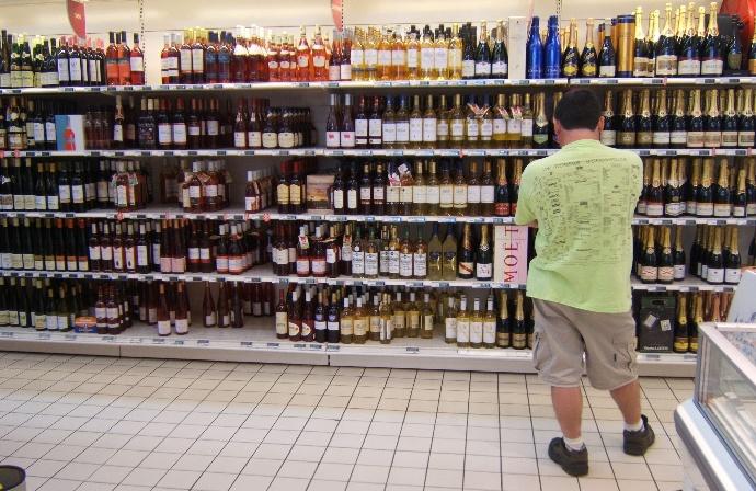 Homme qui n'arrive pas à choisir devant un linéaire de vin